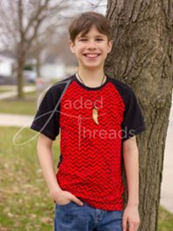 A tween boy with brown hair smiles while looking at the camera. He has his hand